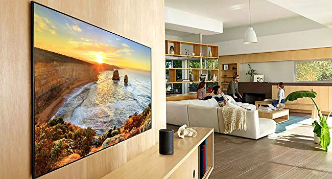 QLED TV hanging on a wall in a living room