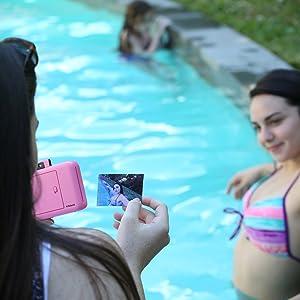 girl looking at print from pink camera