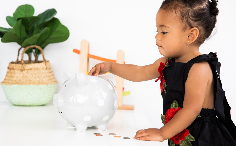 Image of young girl putting coins into piggy bank. Bank makes great gift and educational tool.