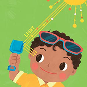 A brown-skinned toddler looks at his shovel; light bounces off it