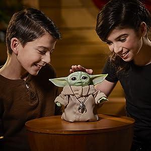 Boneco baby Yoda com duas crianças ao lado