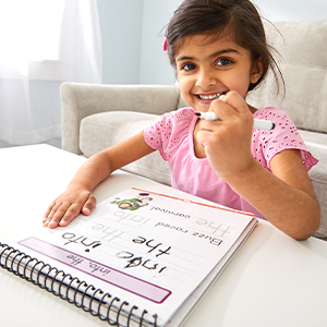 A child holding a disney learning workbook