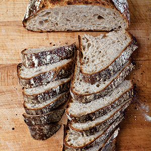 Photograph of sliced baked bread loaf on wooden cutting board.