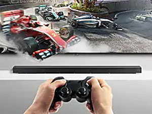 Someone playing a racing game on a QLED with the Soundbar below.