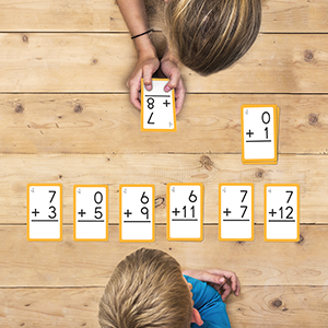 Children playing a game with math flash cards