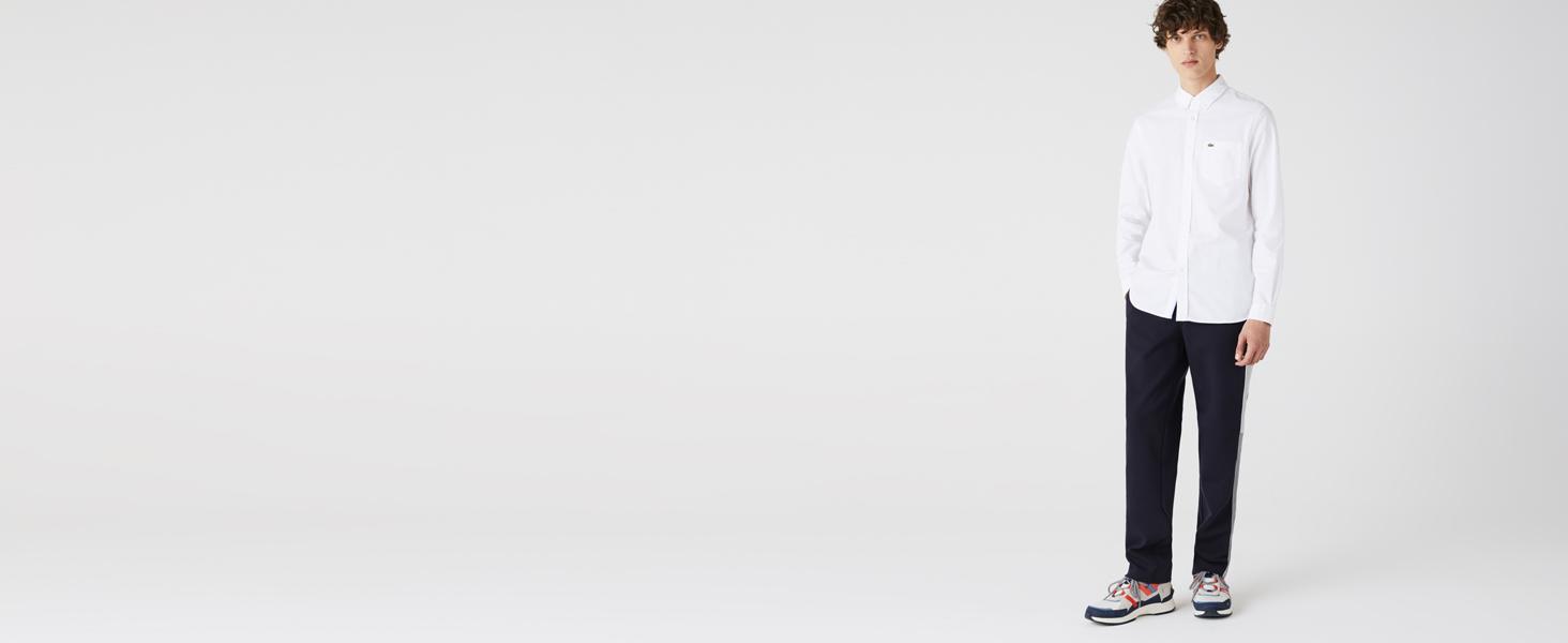 Hombre con camisa blanca, pantalón negro y zapatillas Lacoste