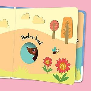 Open view of Peek-a-boo Little Dog! showcasing the peep-through windows throughout the book.
