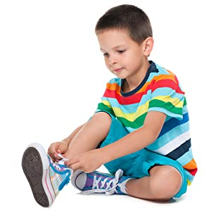 4 year old boy with stripy t-shirt tying his own shoelaces