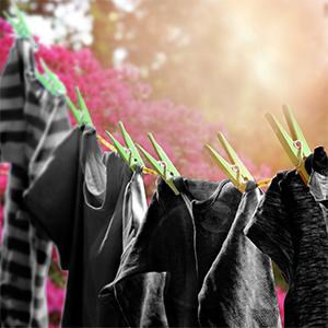 Een waslijn met vlekkeloos schone, donkergekleurde t-shirts, buiten aan het drogen in de zon
