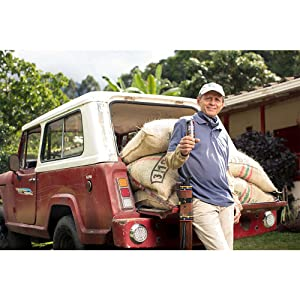 Man leaning against a jeep holding High Brew Coffee tin