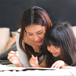 a mother helping her child at home with school work