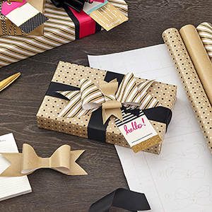 Box wrapped in brown kraft wrapping paper with handmade gift bows and ribbon using gift wrap scraps