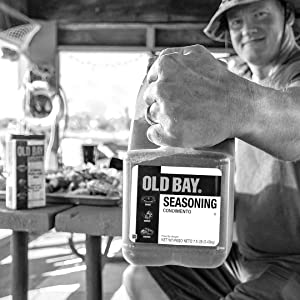 Crabber holding up big container of Original Old Bay Seasoning