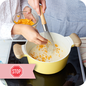 Image of young girl adding grated cheese to a sauce pan.