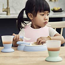 green and blue cups in the shot with a girl eating from the blue plate with a spoon and fork
