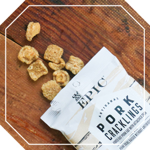 Opened Epic pork cracklings snack bag on a wooden table
