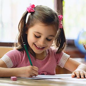 A preschool-aged girl writing in a workbook