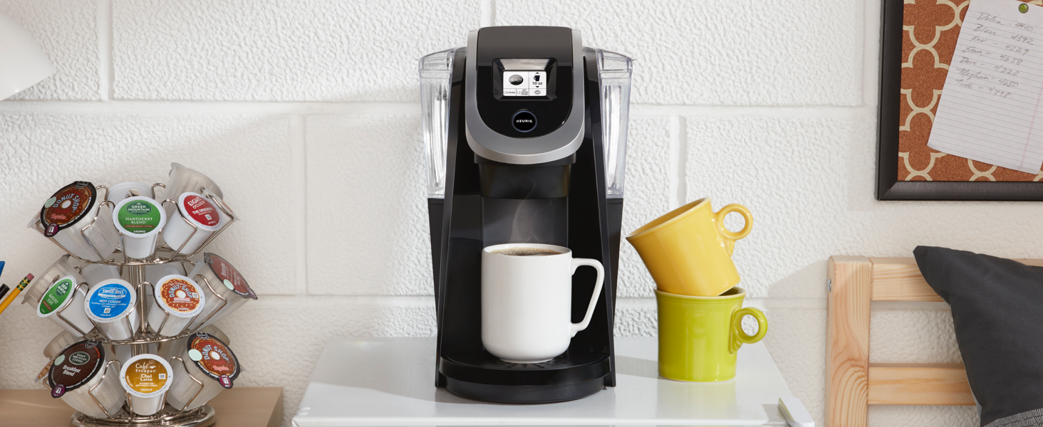 keurig k250 on white countertop next to coffee mugs and k-cups