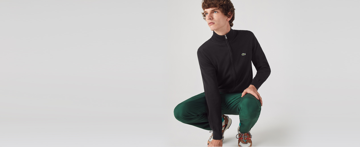 Man in black zip pullover and green Lacoste joggers