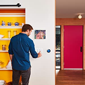Man pressing a Wemo Light Switch 3-Way to turn on a light