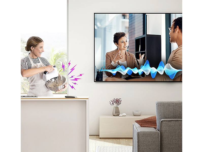 Woman watching TV from the kitchen while using an electric mixer