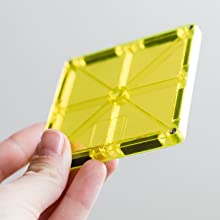 Translucent vibrant yellow Magna-Tile magnetic building tile held at an angle against white wall