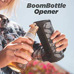 Boom bottle opener opening a beer with one hand on a bluetooth wireless speaker