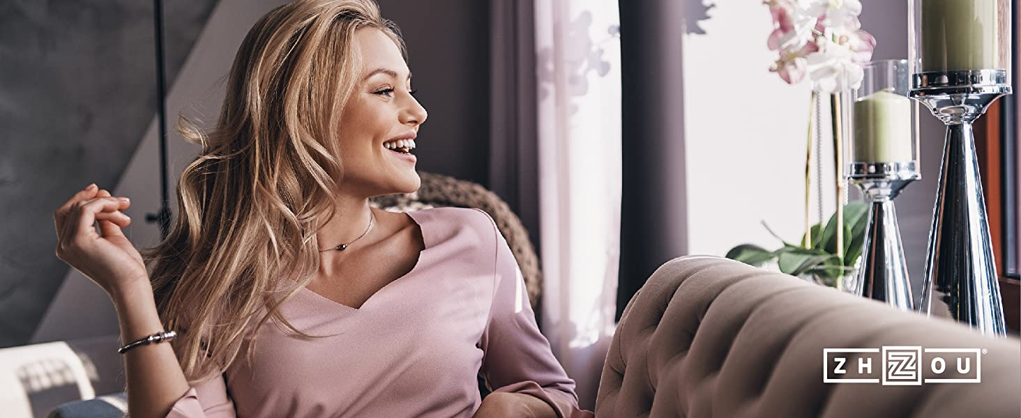 woman looking out sunny window while sitting on a couch smiling