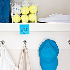 A Post-it Note reminder hanging on a shelf next to sports equipment.