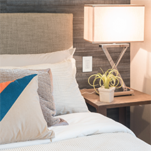 Bed and bedside table with lamp featuring the HALO Home multi-room scene pad