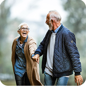 Older couple enjoy a brisk walk in the park, while holding hands.