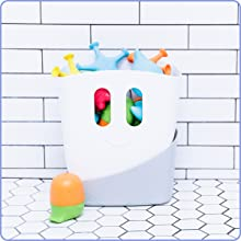 Ubbi bath gift set on tiled bathroom floor with toy drying bin filled with Ubbi bath toys