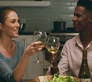 Couple toasting wine glasses while eating dinner