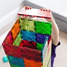 Translucent red large square magnetic tile safely held in child's hand as she places it on a tower
