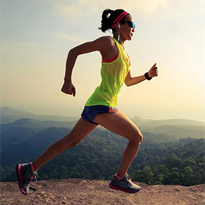 woman running on a trail hiking and listening music with nuforce be sport4 bluetooth earbuds