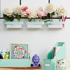 fake roses in styrofoam in clear caddy mounted on wall above a desk