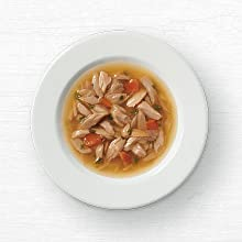 Small shreds of chicken and carrots in broth