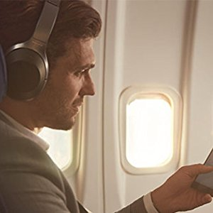 A man sitting on an aeroplane wearing WH-1000XM2 headphones looking at his phone
