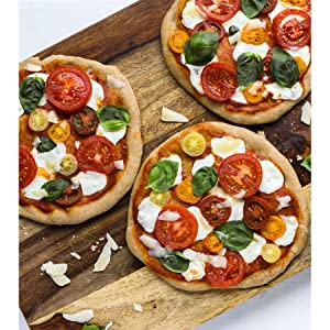3 pizzas on a cutting board covered with sliced fresh tomato and mozzerella