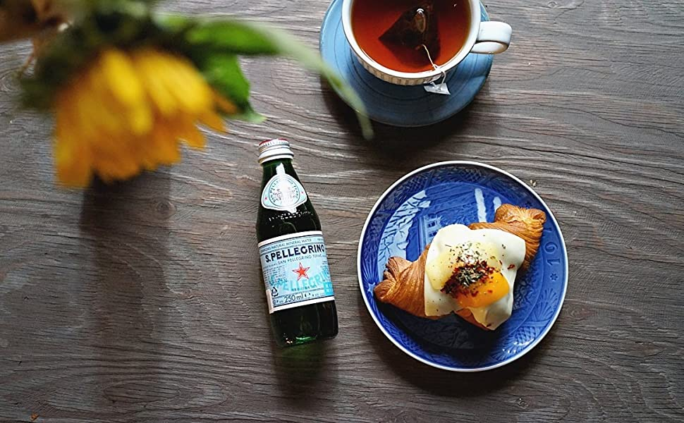 S.Pellegrino Sparkling Natural Mineral Water with croissant and tea.