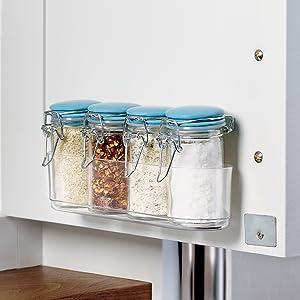 jars of spices in caddy on inside of cupboard door
