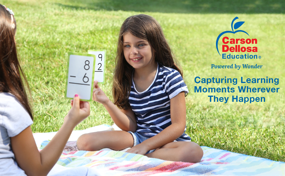 Two girls playing with flash cards in a park