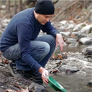 man crouching near river with a green gold panning sifter