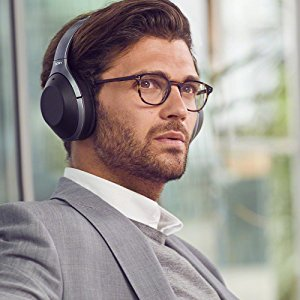 A man in an airport lounge wearing WH-1000XM2 headphones