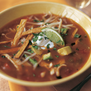 Photograph of cozy bowl Mexican Chicken Soup topped with sour cream and lime wedge