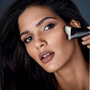 Model applying makeup with brush
