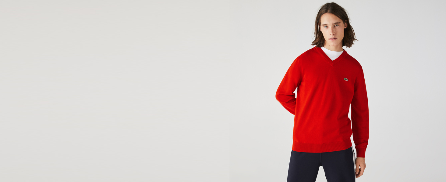 Men's red V-neck sweater over white tee and black tracksuit bottoms