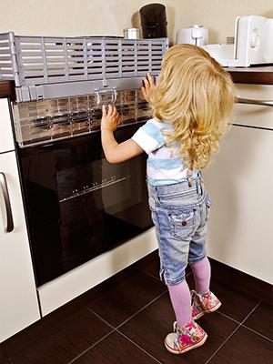Kind versucht auf heiße Herdplatte zu fassen, Herdschutz verhindert dies