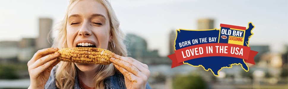 Woman eating corn on the cob sprinkled with Old Bay Seasoning. Born on the Bay. Loved in the USA.