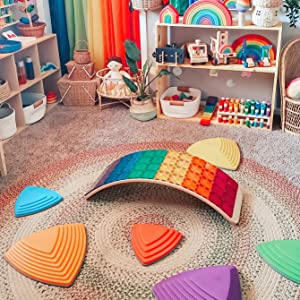 Vibrant rainbow colored Magna-Tiles lay on a wobbel board in the center of a room.